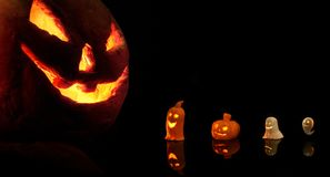 Halloween pumpkin with burning candles on black background Royalty Free Stock Photography