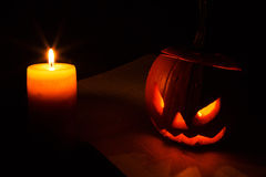 Halloween pumpkin and candle on the book Stock Photos