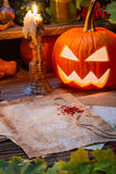 Halloween pumpkin and candle on witch's table Royalty Free Stock Photo