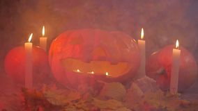 Halloween pumpkin and candles on leaves and smoke stock video footage