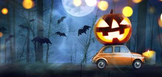 Halloween pumpkin on car. Halloween car delivering pumpkin against night scary autumn forest background stock image