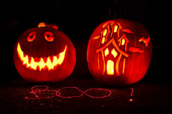 Halloween Pumpkin Carving. Two pumpkins carved - A Face and a Haunted House - Lit by candles. Writing in front created using a laser pointer Royalty Free Stock Image
