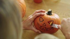 Halloween pumpkin. Close up of woman carving pumpkin for Halloween stock video footage