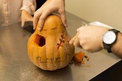 Halloween pumpkin. Creating a Halloween pumpkin, man carving the pumpkin Stock Image