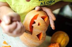 Halloween pumpkin cutting process, process of making Jack-o-lantern. Male hands with knife. Stock Photos