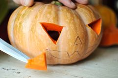 Halloween pumpkin cutting process, process of making Jack-o-lantern. Male hands with knife. Stock Photography