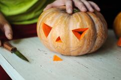 Halloween pumpkin cutting process, process of making Jack-o-lantern. Male hands with knife. Royalty Free Stock Images