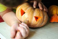 Halloween pumpkin cutting process, process of making Jack-o-lantern. Male hands with knife. Royalty Free Stock Photography