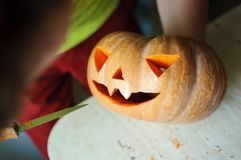 Halloween pumpkin cutting process, process of making Jack-o-lantern. Male hands with knife. Stock Photo