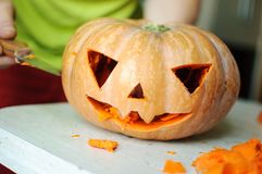 Halloween pumpkin cutting process, process of making Jack-o-lantern. Male hands with knife. Royalty Free Stock Image