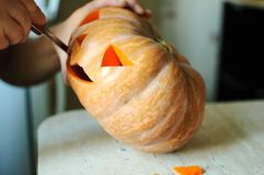 Halloween pumpkin cutting process, process of making Jack-o-lantern. Male hands with knife. Royalty Free Stock Photos