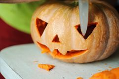 Halloween pumpkin cutting process, process of making Jack-o-lantern. Male hands with knife. Royalty Free Stock Photo