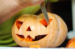 Halloween pumpkin cutting process, process of making Jack-o-lantern. Male hands with knife. Stock Images