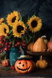 Halloween pumpkin decor with flowers. Halloween pumpkin decor with autumn flowers stock photo