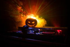 Halloween pumpkin on a dj table with headphones on dark background with copy space. Happy Halloween festival decorations and music royalty free stock images