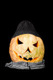 Halloween pumpkin dressed with scarf and cap. Stock Photo