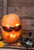 Halloween pumpkin in eyeglass with fishing tackles Royalty Free Stock Image
