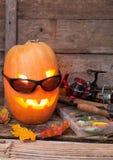 Halloween pumpkin in eyeglass with fishing tackles Stock Photo