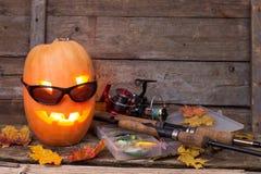 Halloween pumpkin in eyeglass with fishing tackles Royalty Free Stock Photos