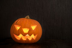 Halloween pumpkin with fire candle glowing on dark backdrop with Royalty Free Stock Photo