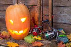 Halloween pumpkin with fishing tackles Stock Photography