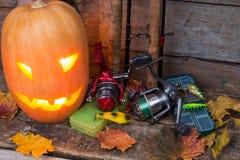 Halloween pumpkin with fishing tackles Royalty Free Stock Image