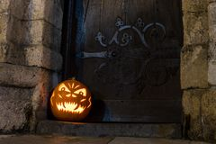 Halloween pumpkin in front of ancient wooden door and stone wall of a church, Germany Royalty Free Stock Image