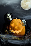 Halloween Pumpkin & Ghoul in Mist. A smiling Halloween pumpkin being hugged by a ghostly ghoul, mist and cobwebs in foreground and full moon and wispy clouds in stock image