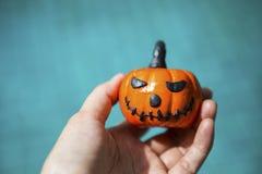 Halloween pumpkin in girl hand over blurred blue water background Stock Photos