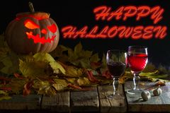 Halloween pumpkin with glasses of wine, garlic, and autumn leave royalty free stock photo