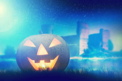 Halloween pumpkin glowing in dark, misty scenery Stock Image