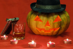 Halloween. Pumpkin with glowing eyes. Pumpkin for Halloween with glowing eyes and a glass of whiskey Stock Photo