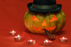 Halloween. Pumpkin with glowing eyes. Pumpkin for Halloween with glowing eyes and smoking pipe Stock Photo