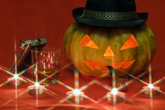 Halloween. Pumpkin with glowing eyes. Pumpkin for Halloween with glowing eyes, smoking pipe and glass of whiskey by candlelight Royalty Free Stock Photography