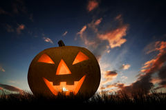Halloween pumpkin glowing under dark sunset, night sky. Jack o'lantern Royalty Free Stock Images