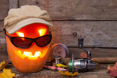 Halloween pumpkin in hat with fishing tackles Stock Photos