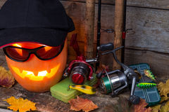 Halloween pumpkin in hat with fishing tackles Royalty Free Stock Photo