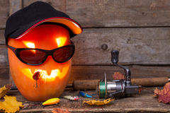 Halloween pumpkin in hat with fishing tackles Stock Image