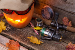 Halloween pumpkin in hat with fishing tackles Royalty Free Stock Images