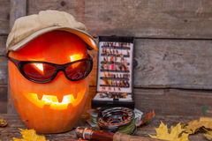 Halloween pumpkin in hat with fly-fishing tackles Stock Photography