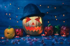 Halloween pumpkin in hat, with scary peppers, candles, mystical. Illumination, smoke, fod is on the background stock photography