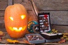 Halloween pumpkin head with fly-fishing tackles Stock Image