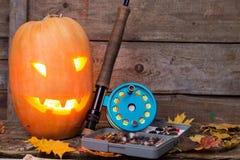 Halloween pumpkin head with fly-fishing tackles Royalty Free Stock Photo