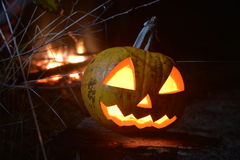 Halloween pumpkin head jack with fire on the background. Flaming Halloween Pumpkin under the moonlight in  dark forest Royalty Free Stock Photo