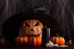 Halloween pumpkin head jack lantern with big black witch hat. On the background of cobwebs Royalty Free Stock Photography