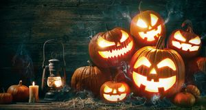 Halloween pumpkin head jack lantern with burning candles. In scary deep night stock photos