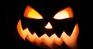 Shining jack-o-lantern. Halloween pumpkin with scary face isolated on the black background. Halloween pumpkin head jack lantern with burning candles over black stock video footage