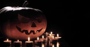 Halloween pumpkin head jack lantern with burning candles over black background. Halloween holidays art design stock video footage