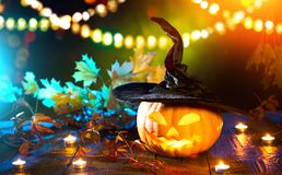 Beauty model girl in colorful bright lights with trendy makeupHalloween pumpkin head jack lantern with burning candles Royalty Free Stock Photo