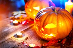 Beauty model girl in colorful bright lights with trendy makeupHalloween pumpkin head jack lantern with burning candles Stock Image